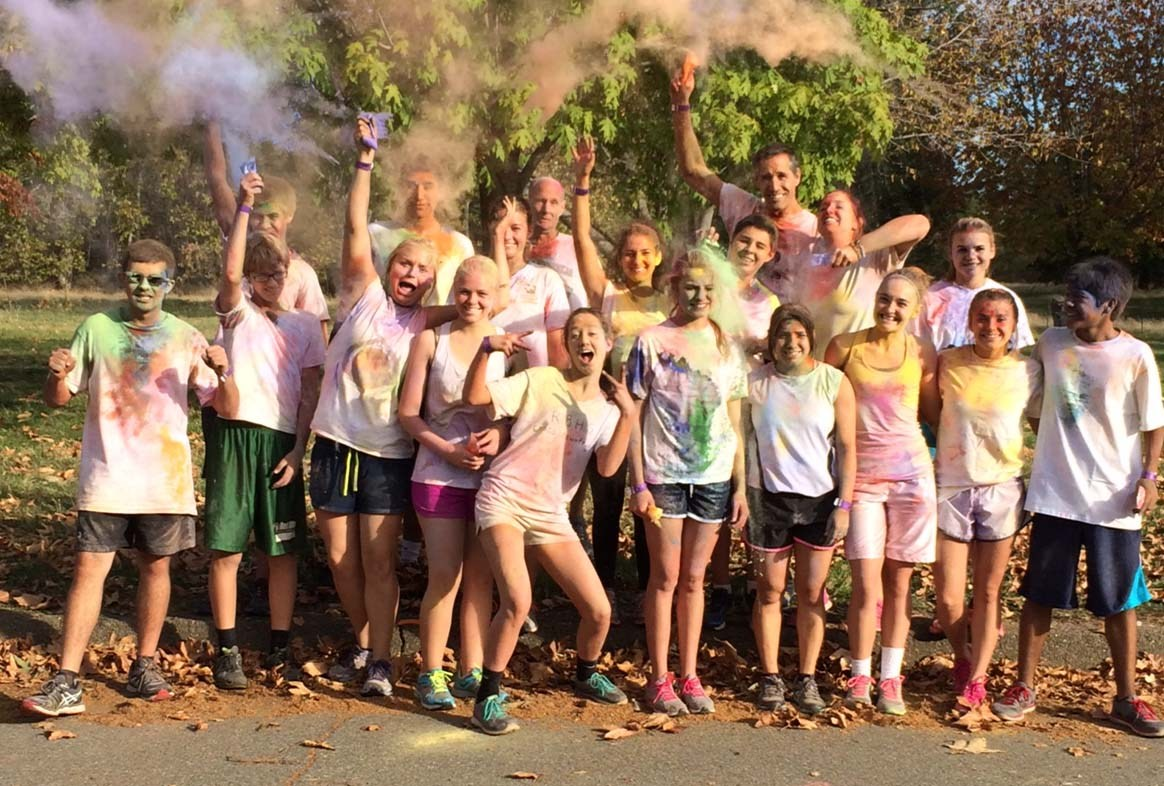 students and staff covered in color chalk